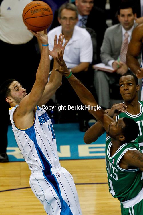 December 28, 2011; New Orleans, LA, USA; New Orleans Hornets guard Greivis Vasquez (21) shoots over Boston Celtics guard Keyon Dooling (51) during the fourth quarter of a game at the New Orleans Arena. The Hornets defeated the Celtics 97-78.  Mandatory Credit: Derick E. Hingle-US PRESSWIRE
