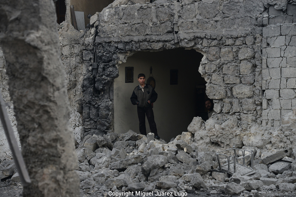 Aleppo, Syria, January 2013 - Two young men stand stunned just minutes after a Syrian government bomb blasted a hole in their house in the neighborhood of Jasmati. Two children of their neighbors were killed in the attack. (Photo by Miguel Juárez Lugo)