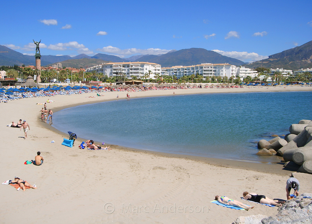 A beach with mountains in the background, Puerto Banus, Marbella, Spain.