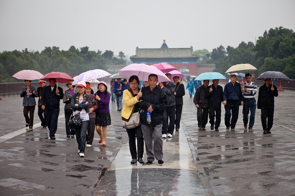 "A group of tourists with umbrellas entering during a rainy day the area at ""The Temple of Heaven"" which is a complex of Taoist buildings situated in the southeastern part of central Beijing. Beijing is the capital of the People's Republic of China and one of the most populous cities in the world with a population of 19,612,368 as of 2010."