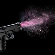 Colorful makeup powder being shot from a Glock handgun