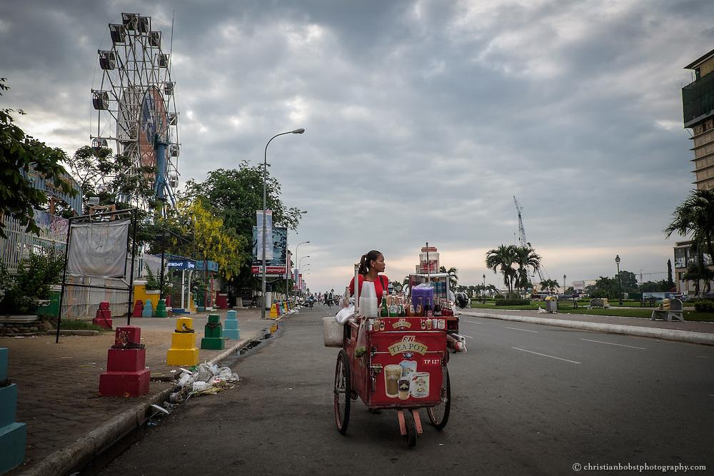 Schon morgens um sieben sind beim Chea Sim Park in Phnom Penh Getränkehändler mit ihren Karren unterwegs.  Im Hintergrund das Riesenrad des Vergnügungsparks Dream Land.