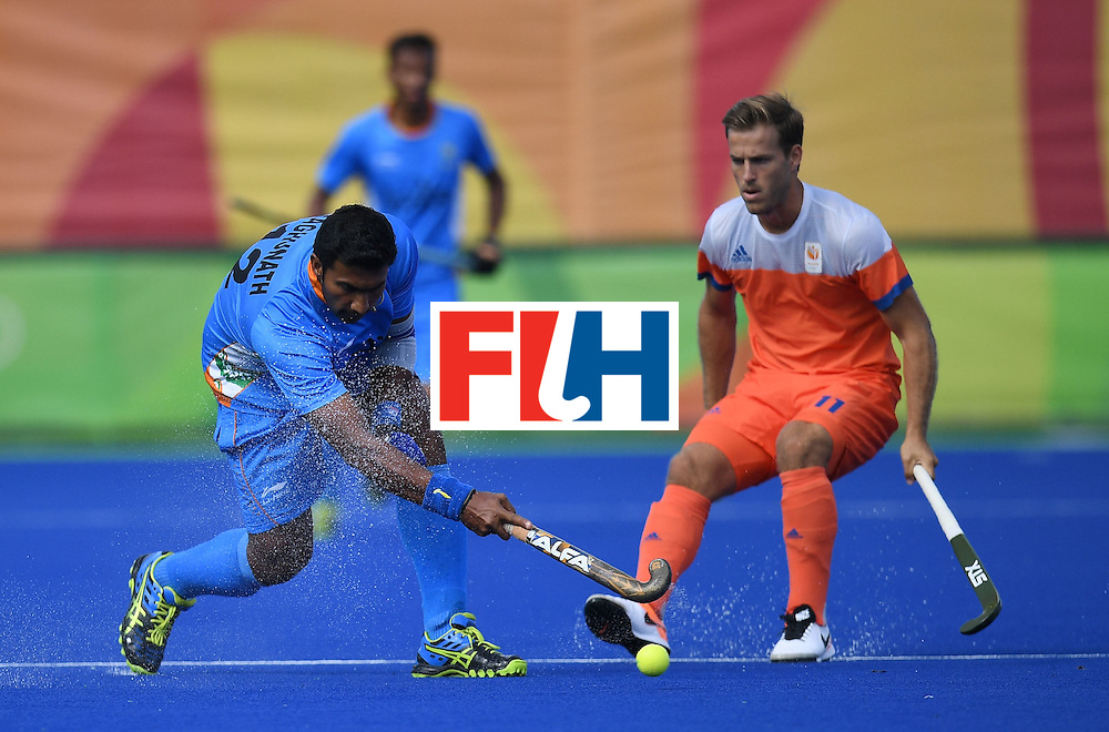 India's Raghunath Vokkaliga hits the ball as the Netherland's Jeroen Hertzberger looks on during the men's field hockey Netherland's vs India match of the Rio 2016 Olympics Games at the Olympic Hockey Centre in Rio de Janeiro on August, 11 2016. / AFP / MANAN VATSYAYANA        (Photo credit should read MANAN VATSYAYANA/AFP/Getty Images)