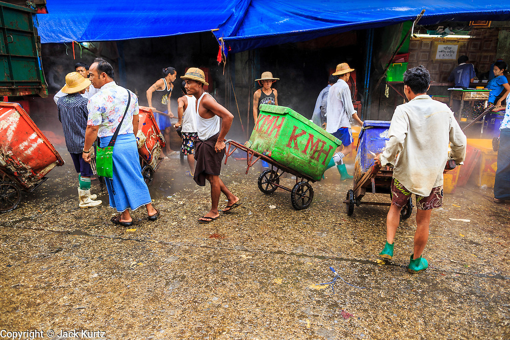 09 JUNE 2014 - YANGON, MYANMAR: Porters line up for crushed ice in the San Pya Fish Market (also spelled Sanpya). The crushed ice is used to pack around the fish sold on the piers in the market. San Pya Fish Market in Yangon is one of the largest wholesale fish markets in Yangon. The market is busiest in early in the morning, from before dawn until about 10AM.    PHOTO BY JACK KURTZ