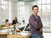 Man standing in kitchen smiling (portrait)