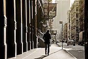 A guy walks on a street of SoHo, Manhattan, New York.