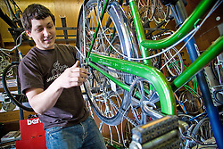 Beau Layman of ReBike, a bicycle-reuse organiziation, makes adjustments to this Schwinn bicycle after replacing the tire tubes for a customer.