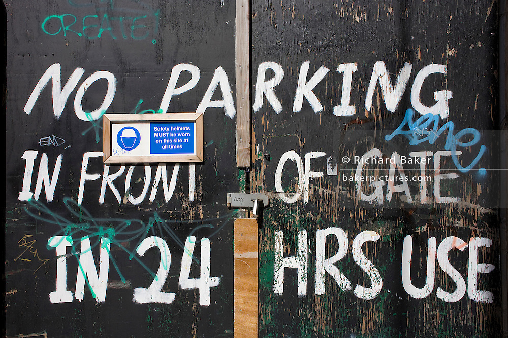 A makeshift sign on a house's gate with graffiti tells car drivers `No Parking in use' 24/7 off Camden High Street.