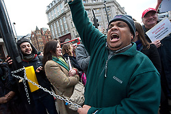 © licensed to London News Pictures. London, UK. 28/01/12. Protestor chants while chained to lampost. Disability cuts protestors chain themsevles to street furniture at Oxford Circus, shutting down traffic on Regent Street. Photo credit: Jules Mattsson/LNP