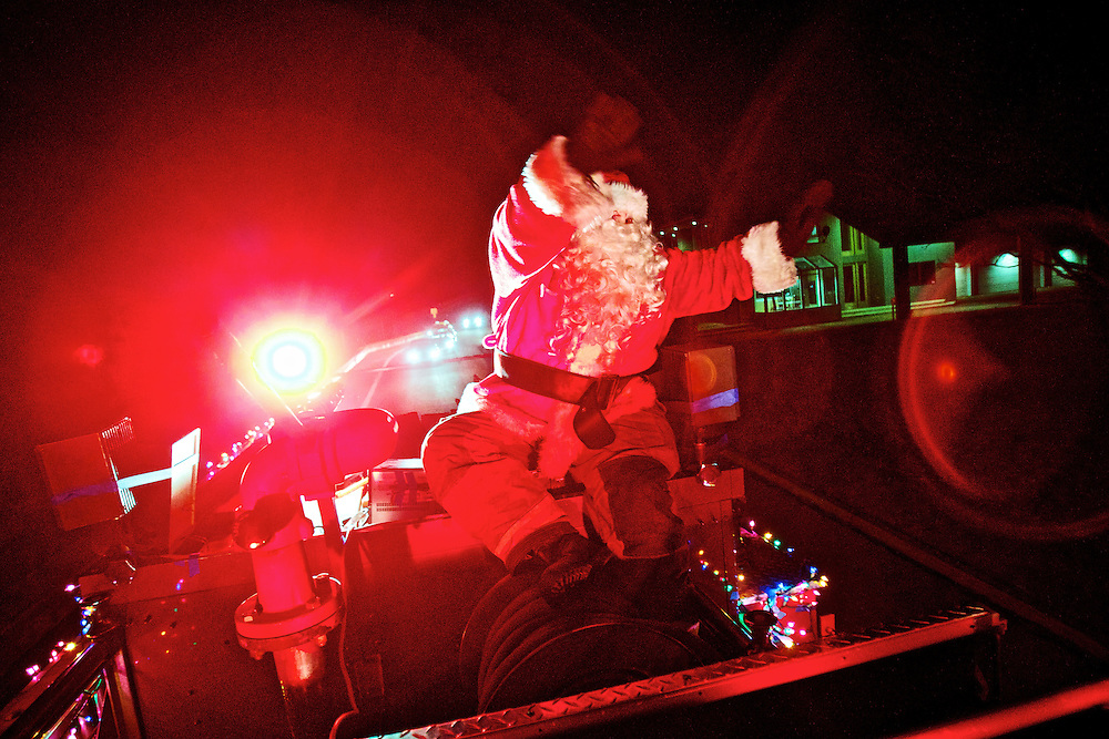 Santa Claus waves to residents in the Fort Grounds neighborhood while touring the area on top of a fire engine Monday during the first night of the Coeur d'Alene Fire Department's mobile Santa food drive. The fire engine, Santa and his helpers will be touring neighborhoods tonight through Friday collecting food items and spreading holiday cheer with music and a brightly decorated fire engine.