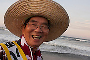 Portrait of a mikoshi supporter wearing a wide brimmed hat during the Hamaorisai Matsuri that takes place on Southern Beach in Chigasaki, near Tokyo, Kanagawa, Japan Monday July 18th 2011. The festivals marks the celebration of Marine Day and the rescuing of a divine image that was washed ashore in the area. Over thirty Mikoshi or portable shrines are carried through the night from surrounding shrines to arrive on the beach for sunrise. There they are blessed and then carried into the surf to purify them.