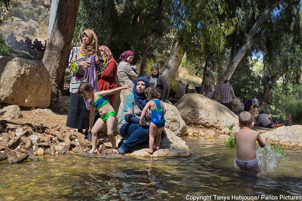 Women enjoy a family picnic, cooling off in the stream at Ein Farha, considered to be one of the most beautiful nature spots in the West Bank. It, like many other nature reserves and heritage sites in the West Bank, is occupied by the Israeli Nature and Parks Authority. Palestinian tourist enterprises are not allowed.