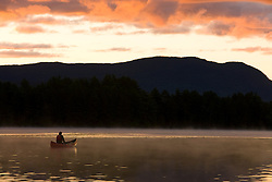 Canoeing at sunrise on Prong Pond near Moosehead Lake Maine USA