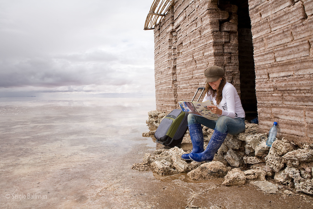 A traveler waits for transport at the entrance of a salt-brick house in the Salar de Uyuni in Bolivia.