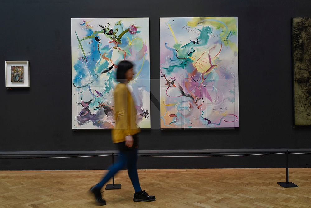 "© Licensed to London News Pictures. 08/06/2017. London, UK. A visitor walks in front of (L to R) ""She Pricked Her Fingers Cutting The Clouds"" and ""Many-Coloured Messenger Seeks Her Fortune"" both by Fiona Rae RA. Preview of the Summer Exhibition 2017 at the Royal Academy of Arts in Piccadilly.  Co-ordinated by Royal Academician Eileen Cooper, the 249th Summer Exhibition is the world's largest open submission exhibition with around 1,100 works on display by high profile and up and coming artists.<br />  Photo credit : Stephen Chung/LNP"