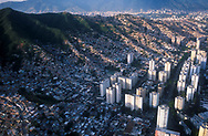 La vista aérea de las zonas marginales de la ciudad de Caracas. Muestra las miles de casas construidas cerro arriba. A sus pies, los edificio que son rodeados por la sobre población. Caracas, 19 - 09 - 2005 (Ramón Lepage / Orinoquiaphoto)  )   Aerial view the city of Caracas. The city with its Modern arquitecture, Highways and contrast between the rich and poor neighborhoods is surrounded by the Avila National Park and many hills around the valley where the shanty Towns or ´´barrios¨ have grown to become one the largest in Latin America.  (Ramón Lepage / Orinoquiaphoto)..
