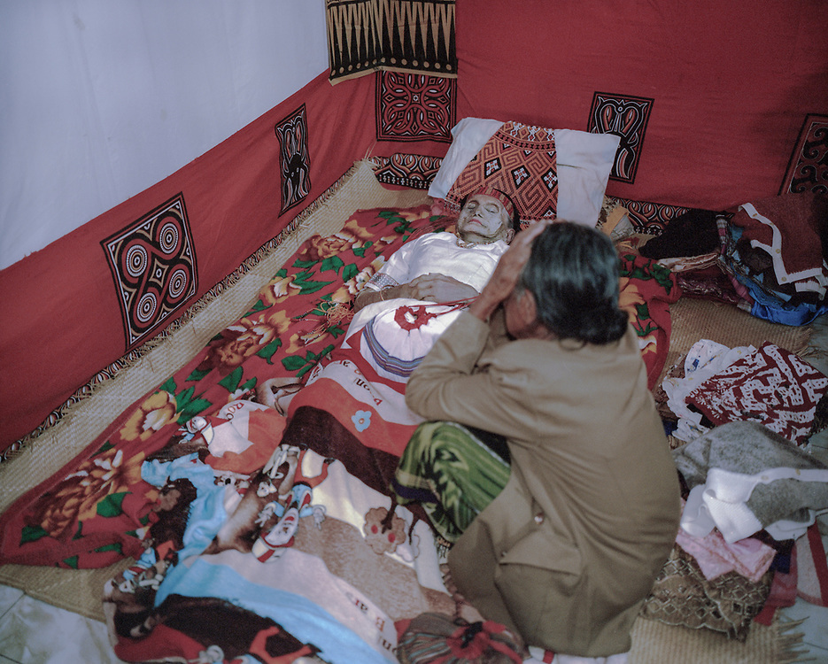 In Torajan culture, death is not necessarily the end.  The body of Lai' Tiku who passed on a few months ago is seen in her home.  She is surrounded by her personal belongings which will be placed inside her coffin, a family member grieves next to her.  The matriarch in her family, Nenek Lai' Tiku passed away at age 102, she is survived by 10 children, 49 grandchildren, and 162 great-grandchildren.