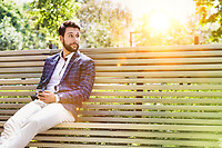 Portrait of young attractive businessman using smartphone while sitting on bench