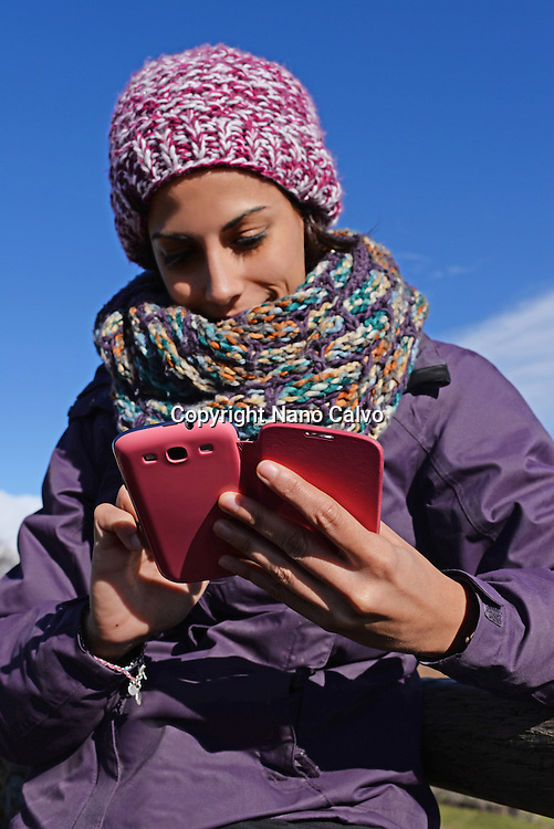 Young woman using mobile phone in winter environment