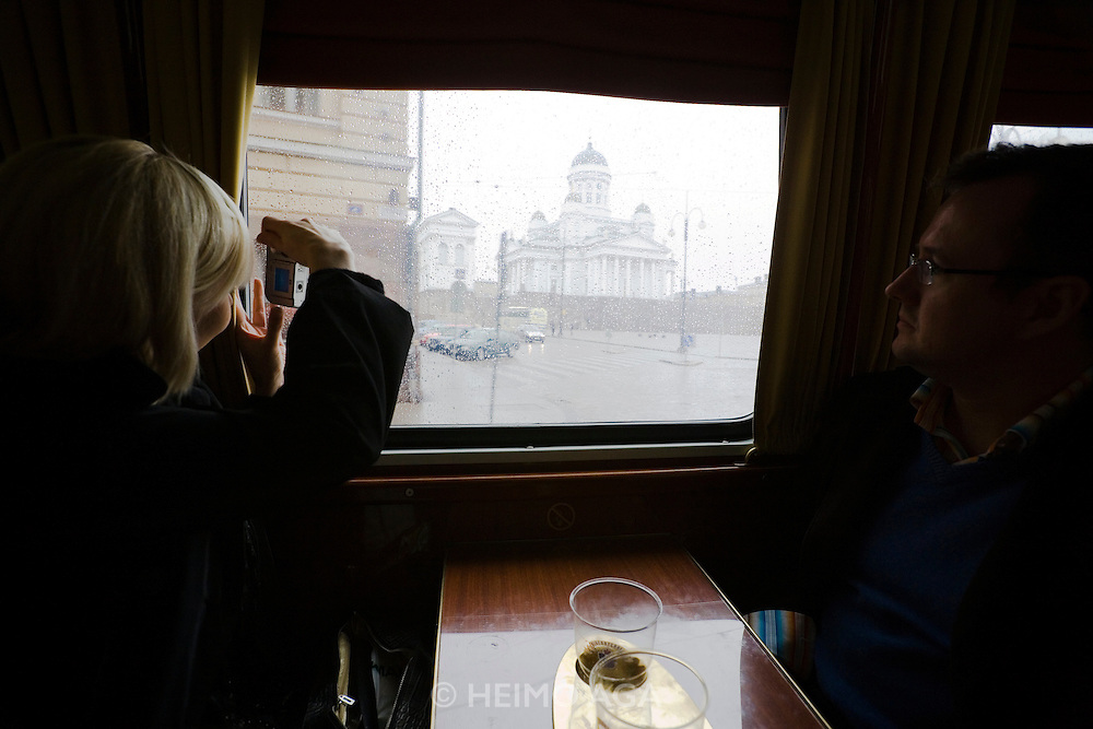 Tourists enjoying a city tour on a rainy day aboard Sparakoff, the fiery red Pub Tram operated by Koff beer brewery. Passing the lutheran cathedral at Senate Square.