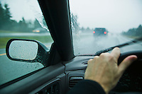A first person / drivrs perspective of driving on a freeway in the rain.