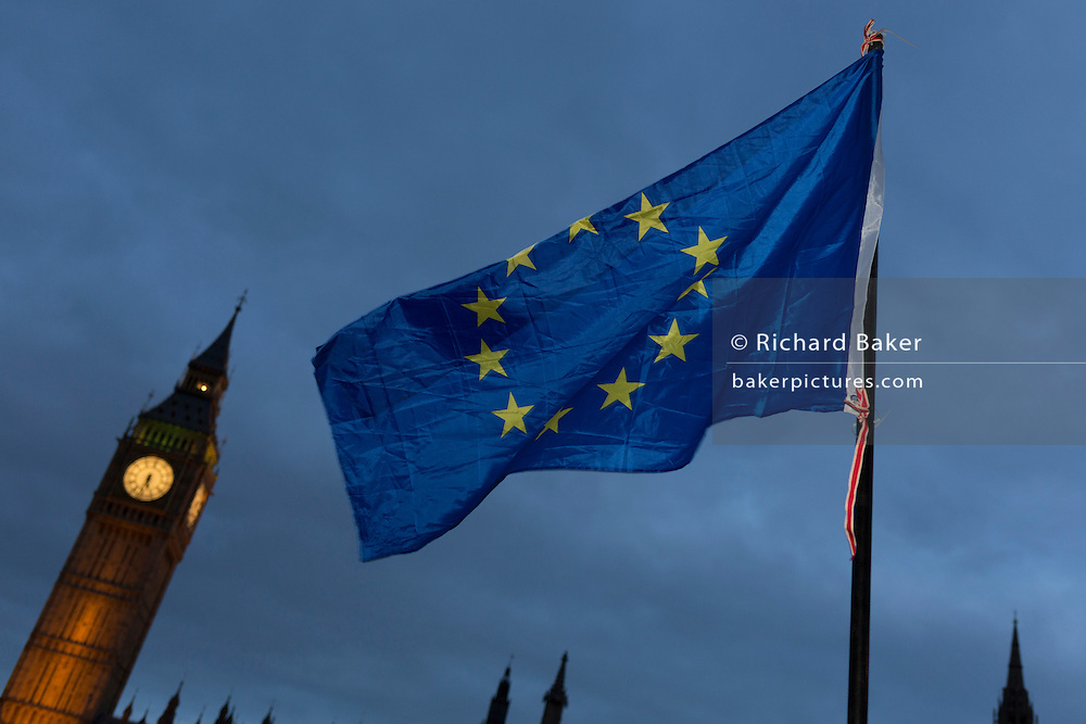 "An EU flag is waved in front of the British parliament as the British government debated US President Donald Trump's state visit to the UK, thousands of protesters gathered in large numbers against the trip which would potentially cost millions of Pounds in security alone, on 20th February 2017, in Parliament Square, London, UK. The visit comes after two online petitions received more than the 100,000 signatures required for such a debate to be considered in Parliament. A petition against the state visit got 1.85m signatures, while one supporting it got 311,000. Campaigners protested against the ""hatred, racism and division that Donald Trump is trying to create"". Prime Minister Theresa May announced the state visit during her visit to Washington in January."