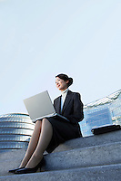 Businesswoman Using Laptop on outdoor Steps