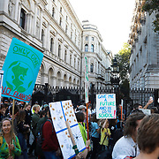 Tens of thousands took to the streets in Central London taking part in the the Global Climate Strike, September 20th 2019, London, United Kingdom.  The protest passing Downing Street 10. After the speeches people marched through Parliament Square and Whitehall to let the Government hear their demands. The day of strike for the climate was a global event with millions taking part across the globe. The strike was inspired by Greta Thunberg, a Swedish school girl who started the first school strike for the climate. Her action inspired school children across the world to go on strike demanding radical climate change policies to save their future. On September 20th adults aand children alike went out on strike to demand radical political change and climate justice. The day included speeches and a march through central London.
