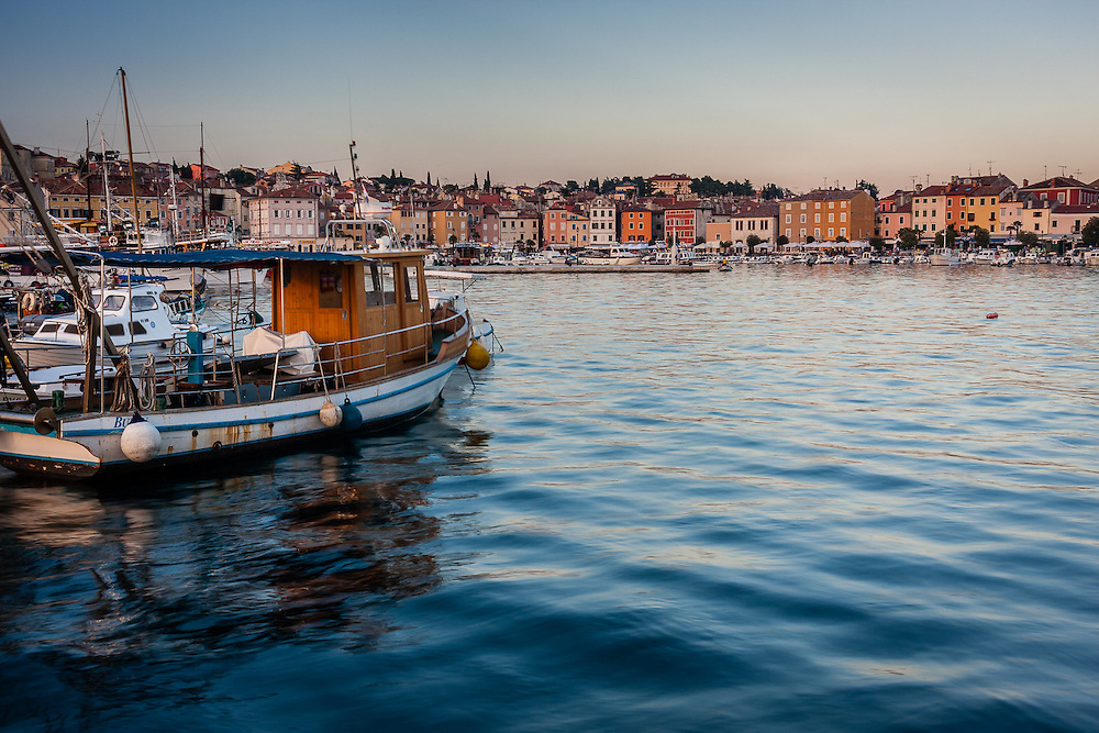 A boat in Rovinj harbour overlooks the city bathed in warm late afternoon light