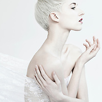 Female with short blonde hair with arms crossed and torso covered in lace looking to side in profile