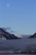 Gibbous moon hangs over glacier and mountains of Smeerenburgfjorden along coast of Spitsbergen island; Svalbard, Norway.