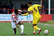 Mathhieu Manset tackles Curtis Nelson during the Sky Bet League 2 match between Cheltenham Town and Plymouth Argyle at Whaddon Road, Cheltenham, England on 28 March 2015. Photo by Alan Franklin.