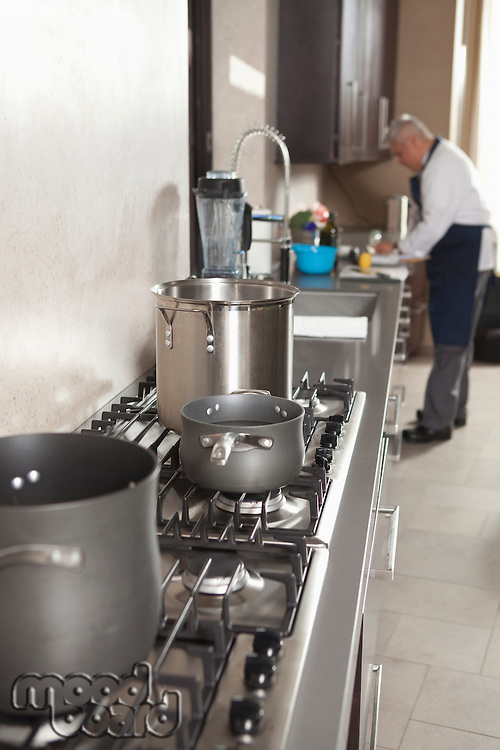 Chef works in kitchen with saucepans on hob