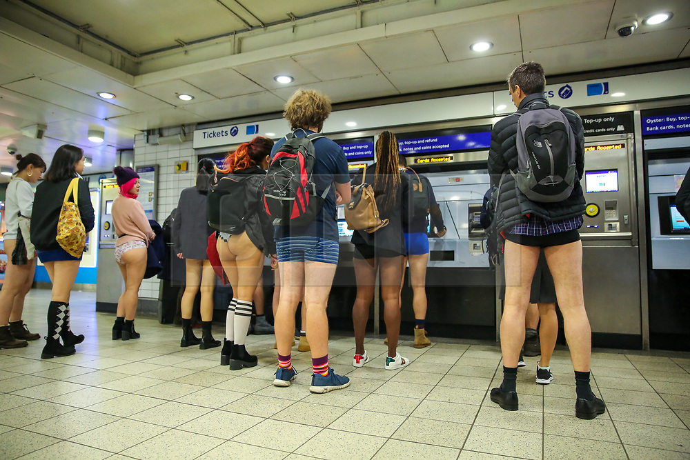 "© Licensed to London News Pictures. 13/01/2019. London, UK. Participants take part in 10th anniversary of 'No Trousers Tube Ride' by buying the travel tickets at Paddington London underground station. The ""No Pants Subway Ride"" is an annual event staged by Improve Everywhere every January in New York City. The mission started as a small prank with seven guys and has grown into an international celebration of silliness, with dozens of cities including London around the world participating each year. Photo credit: Dinendra Haria/LNP"