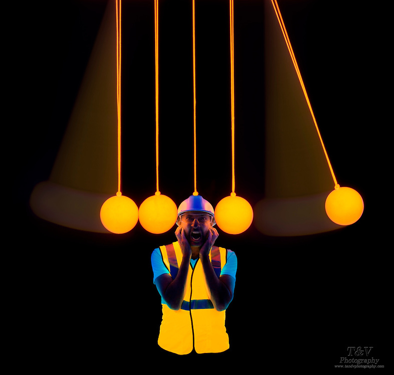 A man wearing a hard hat is the center ball in a glowing Newton's cradle.Blacklight