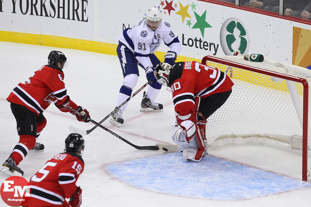 Feb 7, 2013; Newark, NJ, USA; New Jersey Devils goalie Martin Brodeur (30) makes a save on Tampa Bay Lightning center Steven Stamkos (91) while New Jersey Devils defenseman Andy Greene (6) grabs the rebound during the first period at the Prudential Center.
