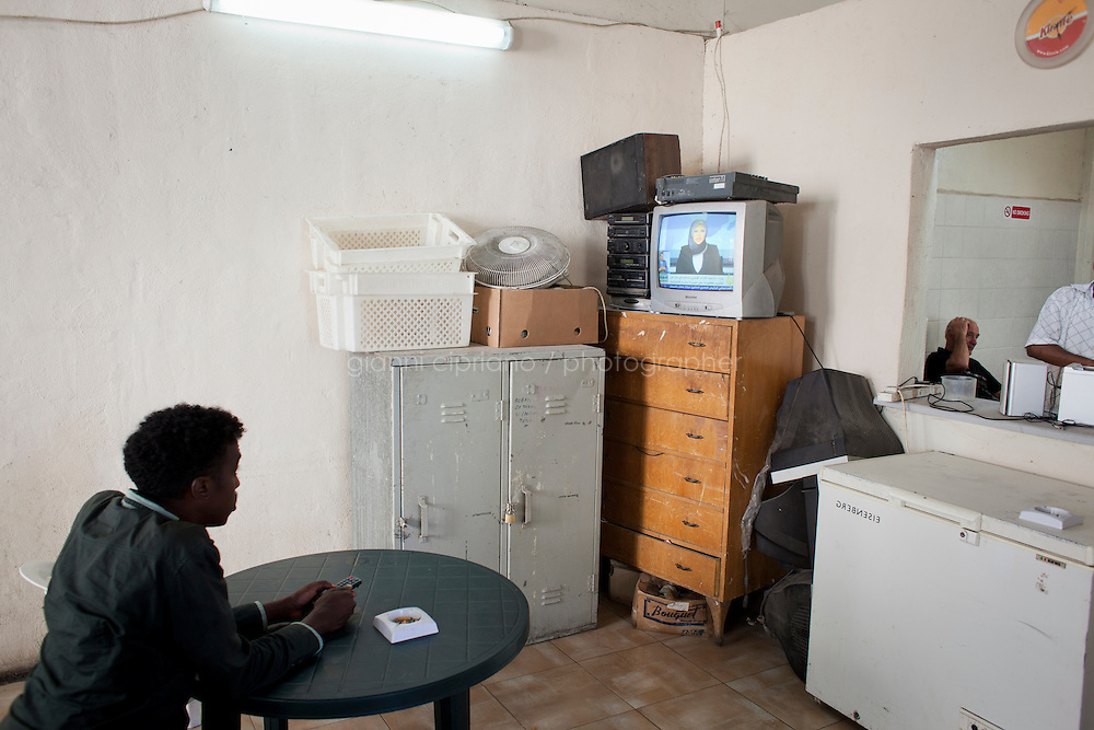 MARSA, MALTA - JUNE 20: An immigrant watches Al-Jazeera on TV in the leisure room of the Marsa Open Centre in Marsa on June 20, 2011. The Marsa Open Centre's capacity is of 650 people, but now hosts 900 immigrants, most of which are from Somalia. The centre's popoulation is composed of immigrants who received subsidary protection, asylum seekers (immigrants who applied and wait for their case to be handled), and rejected asylum seekers. The Open Centres in Malta serve as a temporary accomodation facility, but they ended becoming permanent accomodation centres. All immigrants who enter in Malta illegally are detained. Upon arrival to Malta, irregular migrants and asylum seekers are sent to one of three dedicated immigration detention facilities. Once apprehended by the authorities, immigrants remain in detention even after they apply for refugee status. detention lasts as long as it takes for asylum claims to be determined. This usually takes months; asylum seekers often wait five to 10 months for their first interview with the Refugee Commissioner. Asylum seekers may be detained for up to 12 months: at this point, if their claim is still pending, they are released and transferred to an Open Center.