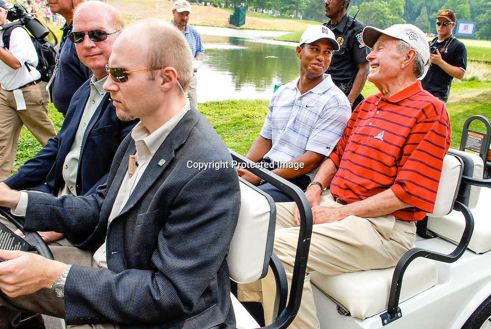 Tiger Woods and former U.S. President George H.W. Bush are driven off the 18th green during the Earl Woods Memorial Pro-Am prior to the start of the AT&T National PGA golf tournament at Congressional Country Club in Bethesda, Maryland.