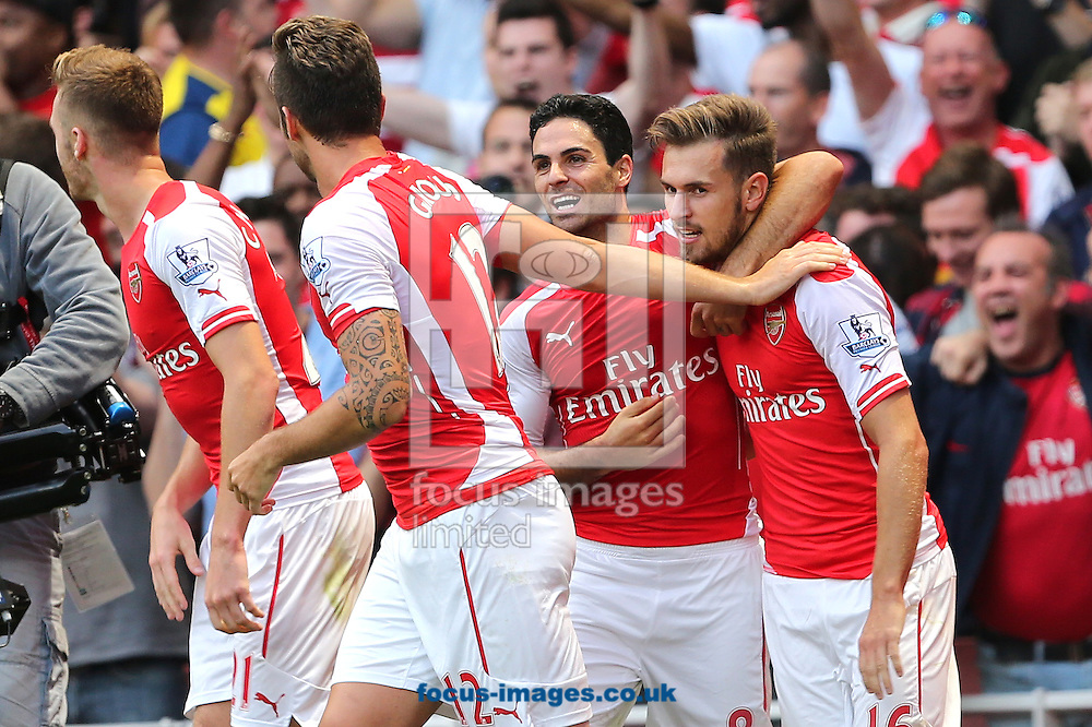 Aaron Ramsey (right) is congratulated by team mates after scoring the winning goal in a 2-1 win over Crystal Palace in the Barclays Premier League match at the Emirates Stadium, London<br /> Picture by Richard Calver/Focus Images Ltd +447792 981244<br /> 16/08/2014