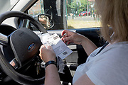 A middle-aged lady follows instructions and shows her personal samples to army personnel from the driver's seat of her car after a self-administered Coronavirus (COVID-19) test in south London. There are four steps to the self-administered Covid-19 test (inserting a swab into the nose and throat) which the public works through in their car, windows up and all communications with army personnel via phone, in a south London leisure centre, on 2nd June 2020, in London, England. The kit provided consists of a booklet, plastic bag, swab, vial, bar codes and a sealable biohazard bag. The swab sample is taken from the back of the throat and nasal passage with the contents sealed and returned to soldiers through a narrow window. The whole process takes between 5-10mins with results available with 48hrs.