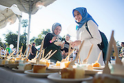 Esra Ibil, left, and Yasemin Inceoglu, right, grab a piece of cake before the start of the Bobcathon cake walk on October 5, 2016.