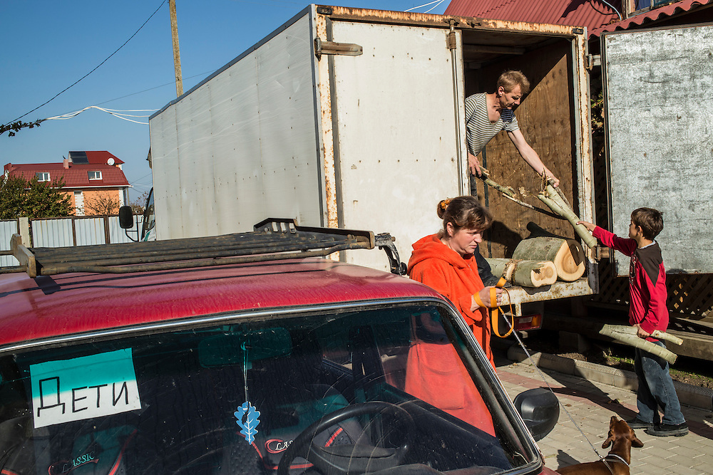 A group of internally displaced people who fled the besieged city of Donetsk unload firewood for winter heating in the small seaside resort that has become their home on Tuesday, October 14, 2014 in Berdyansk, Ukraine. Photo by Brendan Hoffman, Freelance