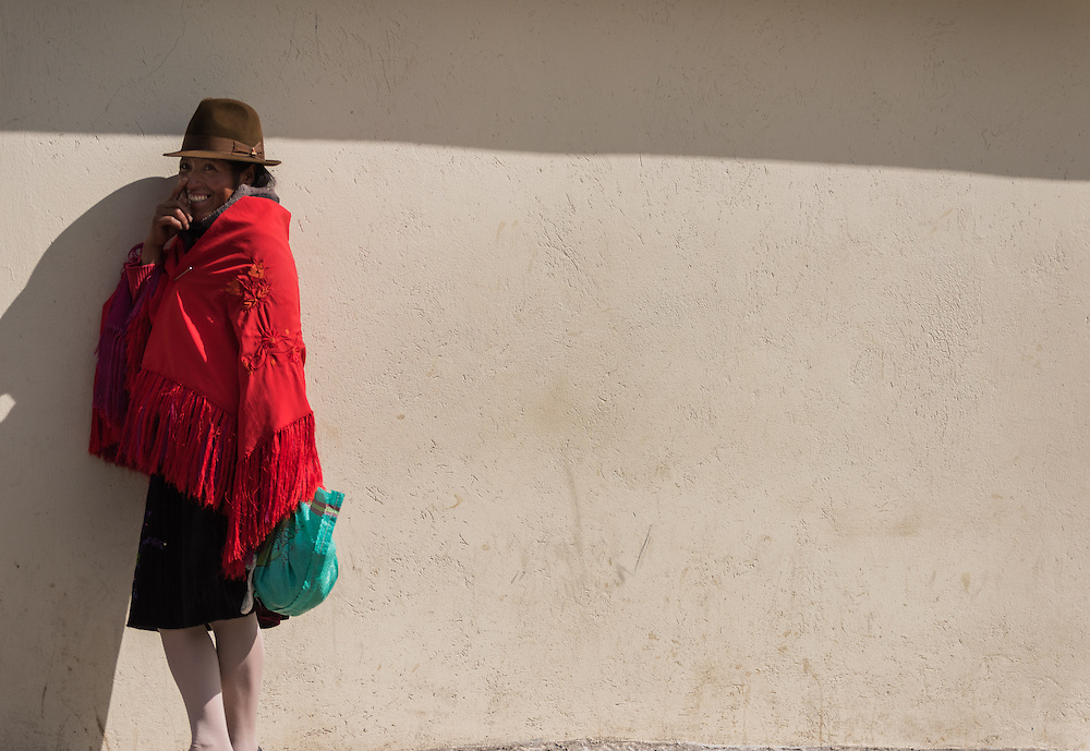 A woman wearing a traditional red scarf and hat in the highlands of Ecuador, Zumbahue, Ecuador.