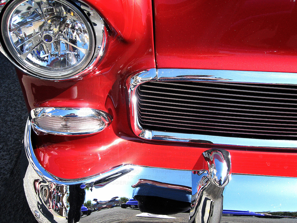 The front of a red car with shiny chrome bumper and grill