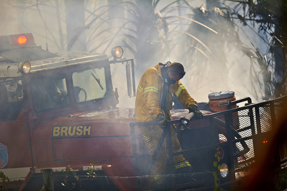 Xavier Mascareñas/Treasure Coast Newspapers; A Martin County Fire Rescue firefighter shows exhaustion while using a firehose on a brush-truck to extinguish flames from a 7-acre fire off Southwest Citrus Boulevard in Palm City on April 25, 2014. A lieutenant working on the other end of the truck suffered a neck injury during the response, and was flown to Lawnwood Regional Medical Center. The department was assisted by the Martin County Sheriff's Office and Florida Forest Service.