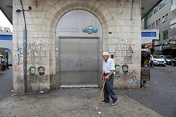 October 1, 2018 - Ramallah, West Bank, Palestinian Territory - A Palestinian man walks past closed shops during a general strike against Israel's Nation State Law, in the West Bank city of Ramallah on October 1, 2018  (Credit Image: © Shadi Hatem/APA Images via ZUMA Wire)