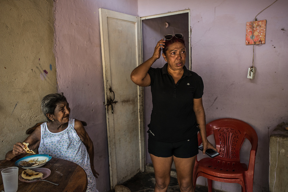 "LA VELA, VENEZUELA - SEPTEMBER 18, 2016: Maria Piñero cries as she says goodbye to her elderly mother, Felipa Palencia de Piñero, who is diabetic. Her mother started to weep uncontrollably telling Maria that it is too dangerous. Maria was especially emotional, because she knew it was likely the last time she would ever see her mother. The family struggles to find the medicine that her mom needs. To escape the crisis, Ms. Piñero spent all of her savings to pay smugglers to take her in a small fishing boat to Curacao island. ""I'm nervous,"" she said. ""I'm leaving with nothing. But I have to do this. Otherwise, we will just die here hungry."" Another benefit of living and working in Curacao, she said, is that she will be able to find and pay for her mother's medicines, and ship them to her in Venezuela. One of the sacrifices of migrating undocumented is that Maria will not be able to return home to visit her mother. PHOTO: Meridith Kohut for The New York Times"