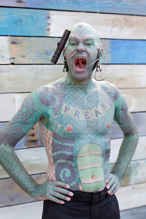 © Licensed to London News Pictures. 24/07/2014. London, England. Pictured: The Lizardman with his full-body tattoo green scales. London Wonderground, produced by Underbelly Productions and the Southbank Centre, returns for a third year to the South Bank. The Wonderground site offers live entertainment, fairground rides and outdoor bars, creating an amusement ground between the Royal Festival Hall and the London Eye. Photo credit: Bettina Strenske/LNP