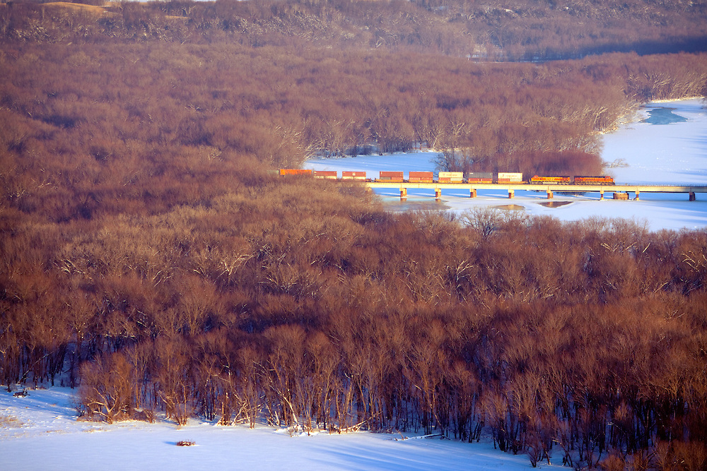 Crossing the Wisconsin River at its confluence with the Mighty Mississippi, a southbound BNSF intermodal train rolls over the low bridge on a cold winter day in the Upper Mississippi River Valley.