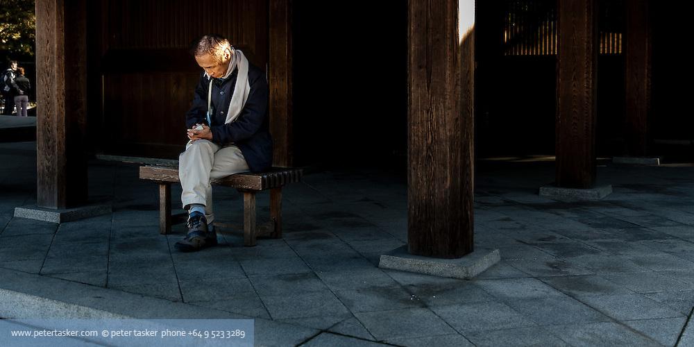 A man meditating at Meiji Shrine, Yoyogi Park, Harajuku, Tokyo, Japan.